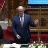 Le premier ministre donne un petit coup avec deux doigts sur le panneau de plexiglas dans la chambre de l'assemblée.