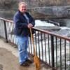 Un homme sur un pont avec une rame à la main.