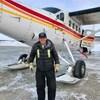Johnny May pose devant un avion.