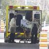 Des ambulanciers s'apprêtent à installer un patient dans une ambulance.