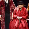 Toute de rouge vêtue, avec un chapeau noir et une canne, Joni Mitchell observe son gâteau d'anniversaire, assise dans un fauteuil.