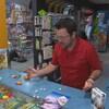Olivier Ménard qui lance des dés sur le comptoir du magasin de jeux et de jouets.