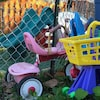 Un tricycle rose et un carrosse en plastique dans la cours d'une garderie.