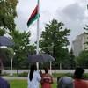 Des gens protégés par des parapluies regardent le drapeau monter.