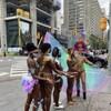 5 femmes portent des maillots deux pièces, des plumes et des paillettes de couleur, au coin d'une intersection achalandée du centre-ville de Toronto.
