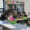 Une salle de classe avec quelques tables disposées en cercle. De jeunes enfants disposés en petits groupes et accompagnés de personnes plus âgées regardent des livres.