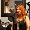 Joy Chapan chante dans un studio d'enregistrement.