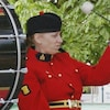 Judy Booth joue du tambour en uniforme militaire, lors d'une fanfare.