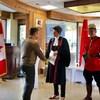 Une juge se tient à côté d'un agent de la Gendarmerie royale du Canada et serre la main d'un homme, elle sourit.