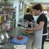 Une femme prépare une salade dans une cuisine industrielle.