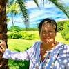 La résidente de West Palm Beach s'appuie sur un palmier.