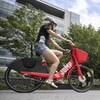 Une femme assise sur l'un des vélos électriques d'Uber.