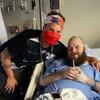 J.D. Burke et Justin Morissette posent pour la caméra alors que M. Morissette est allongé sur un lit d'hôpital.