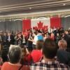 Justin Trudeau un micro à la main prend la parole entourée d'une foule dans une grande salle.