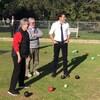 M. Trudeau regarde devant lui sur un terrain gazonné, en compagnie de deux personnes âgées.
