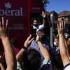Justin Trudeau salue une foule depuis son autobus de campagne.