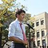 Plan moyen de Justin Trudeau derrière un micro en point de presse dans un parc.
