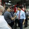 Justin Trudeau serre la main d'un homme dans un garage.