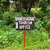 Un panneau dans un champ près d'une forêt.