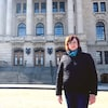 Karen Nurkowski pose à l'extérieur devant l'assemblée législative de la Saskatchewan, à Regina.