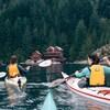 Deux femmes font du kayak en se dirigeant vers une habitation sur la côte.