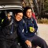 Kevin Papatie et Drake sont assis sur la valise ouverte d'une voiture. Kevin Papatie lève son verre en souriant.