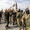 Des militaires en treillis qui brandissent leurs armes et des drapeaux syriens.