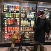 Une dame poussant un petit chariot d'épiceries passe devant des réfrigérateurs contenant du lait dans un supermarché.