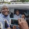 Une foule encercle une voiture dans laquelle se trouve l'ex-président, souriant.