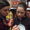 Deux personnes scrutent les étiquettes de produits alimentaires.