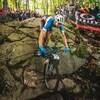 Le cycliste Léandre Bouchard descend une pente dans un sentier se trouvant dans une zone boisée.