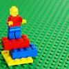 Un personnage jaune, rouge et bleu ancré sur trois briques Lego superposées des mêmes couleurs.