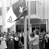 Vieille photo en noir et blanc d'un lever de drapeau devant une foule qui applaudit