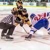 L'arbitre s'apprête à déposer la rondelle sur la glace pour la mise en jeu.