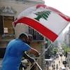 Des hommes attachant un drapeau libanais sur le toit d'un immeuble dans la zone dévastée à Beyrouth.