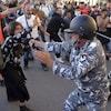 Un policier casqué utilise une matraque à l'encontre d'une femme dans une rue.