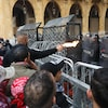 Des manifestants sont derrière des clôtures de métal et des policiers en tenue antiémeute.