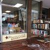 Des livres empilés sur trois étagères devant la  vitrine de la librairie The People's Co-op