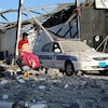 Une femme marche parmi des débris d'un immeuble détruit en transportant un sac. Une voiture de police tâchée de sang est tout près.