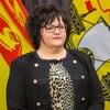 Lisa Harris debout devant des drapeaux du Nouveau-Brunswick.