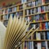 En avant-plan, un livre ouvert devant une bibliothèque bien remplie