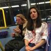 Melania Geymonat, le nez en sang et la chemise tachée de sang, avec son amie, le visage ensanglanté dans un autobus.