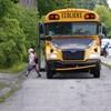 La jeune fille masquée descend de l'autobus scolaire.
