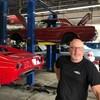 Lou Trottier dans son garage avec des voitures en arrière-plan.