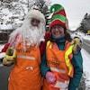 Deux bénévoles, l'un habillé en père Noël et l'autre en lutin, se tiennent côte à côté à l'extérieur en souriant.