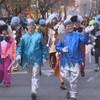 Des gens déguisés en lutins et en clowns prennent part au défilé.