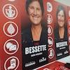 L'attachée assemble des cocardes devant des pancartes électorales de Lyne Bessette
