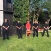Mac Findlay est debout à l'extérieur. De chaque côté de lui se trouvent des pompiers en uniforme.