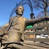 La statue représente le personnage assis sur un banc public.