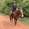 Une femme sur un cheval le long d'un petit chemin de terre dans la forêt.